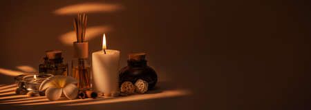 Beautiful spa composition with candles, frangipani flower, oil flasks and other decor elements. Nice warm dark background. Tropical highlights from window. Copy space.