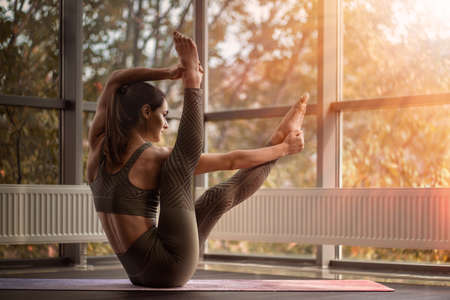 Athletic woman practices yoga. Sun shines through the window