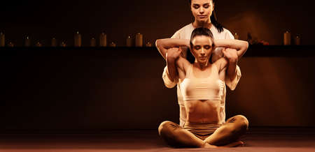 Young fit woman has Thai massage at luxury spa. Warm inviting colors, calm atmosphere, charming light. Copy space Standard-Bild