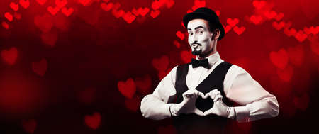 Mime artist showing love sign with hands on red background with heart bokeh. Valentines day concept. Standard-Bild
