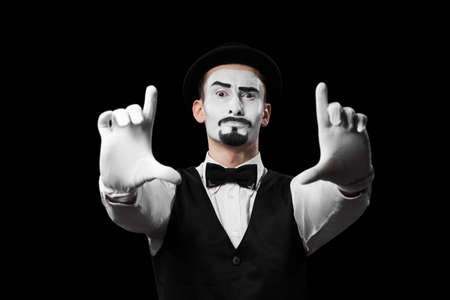 Mime artist showing frame sign with hands isolated on black background.