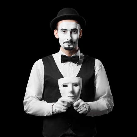 Mime artist holding white mask Isolated on black