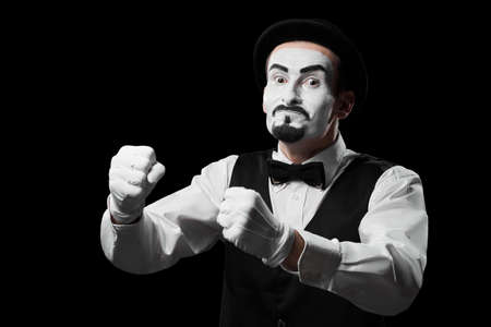 Mime artist shows emotion of anger and rage with facial expression and hands Isolated on black Standard-Bild - 141965537