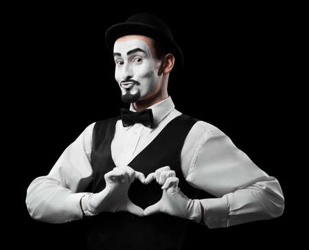 Mime artist showing love sign with hands Isolated on black Standard-Bild