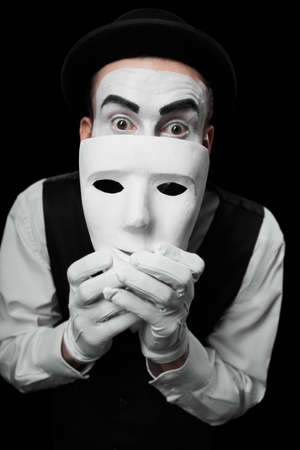Mime artist hiding under white mask Isolated on black
