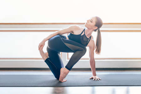 Young fit woman practicing yoga. Sun flare. Copy space. Clear and concise image of morning routine