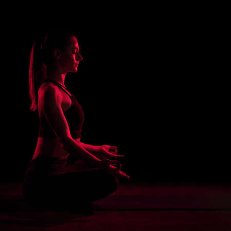 Young fit woman meditating. Neon red light. Modern sci fi representation of yoga. Copy space.