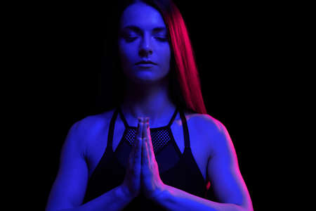 Young fit woman meditating. Neon light. Modern sci fi representation of yoga. Copy space.