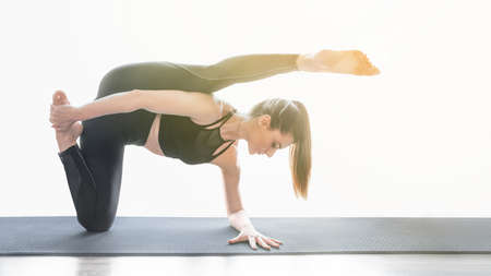 Young fit woman practicing yoga. Sun flare. Copy space. Clear and concise image of morning routine.