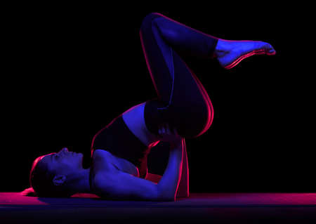 Young fit woman practicing yoga. Neon light. Modern sci fi representation of yoga.