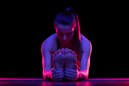 Young fit woman practicing yoga. Neon light. Modern sci fi representation of yoga. Tranquil atmosphere. Copy space. Standard-Bild - 146307353