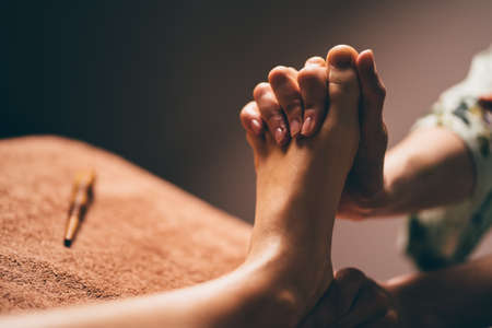 Professional foot massage close up. Authentic shot of luxury spa treatment. Charming light. Shallow depth of field. Stylized and colored. Standard-Bild
