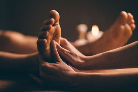 Professional foot massage close up. Authentic shot of luxury spa treatment. Charming light. Shallow depth of field. Stylized and colored. Standard-Bild - 147302704