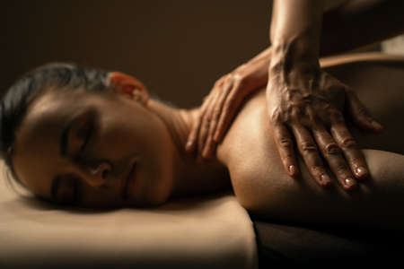 The beautiful girl has massage. Authentic image of luxury spa treatment. Warm colors, charming light. Standard-Bild