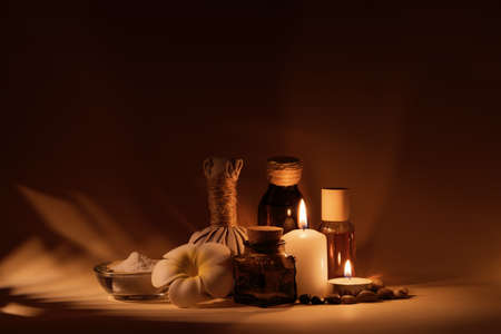 Beautiful spa composition with candles, frangipani flower, oil flasks, bowl with salt and herbal ball. Standard-Bild