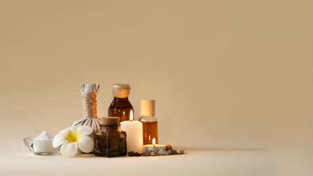 Beautiful spa composition with candles, frangipani flower, oil flasks, bowl with salt and herbal ball. Copy space. Standard-Bild - 156439333