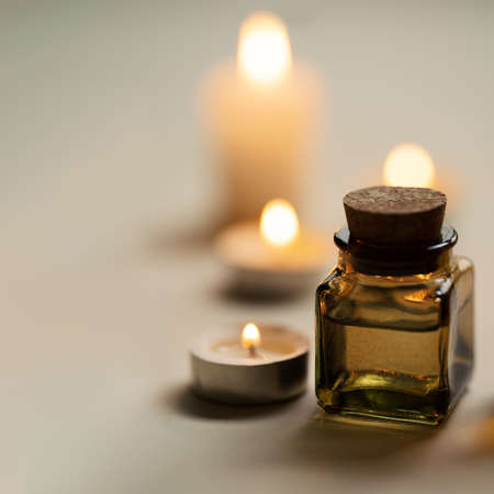 Tranquil and concise spa composition with oil flask and candles. Copy space Standard-Bild - 157035084