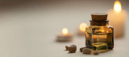 Tranquil and concise spa composition with oil flask, stones and candles. Copy space Standard-Bild - 157034727