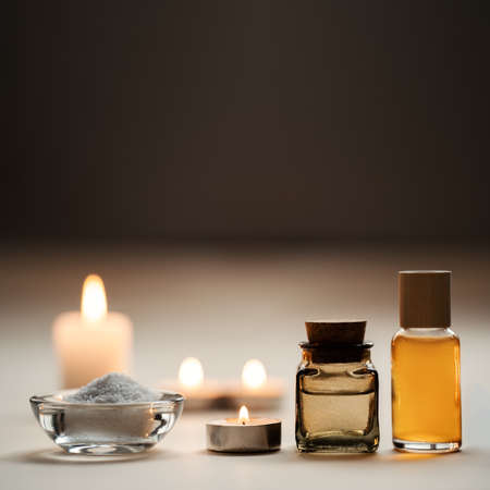 Beautiful spa composition with candles, oil flasks and bowl with salt. Pleasant beige and brown background. Copy space. Standard-Bild - 157034773