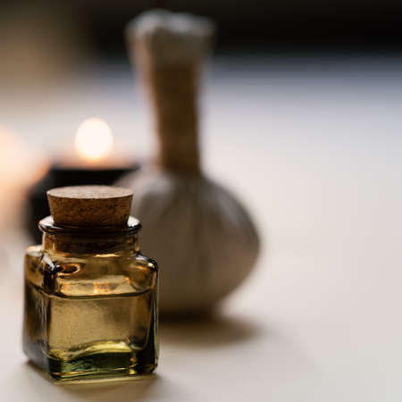 Tranquil and concise spa composition with oil flask, candle and herbal ball. Copy space Standard-Bild - 157034530