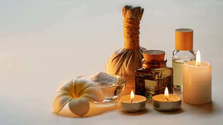 Beautiful spa composition with candles, frangipani flower, oil flasks, bowl with salt and herbal ball. Copy space. Standard-Bild - 157207479