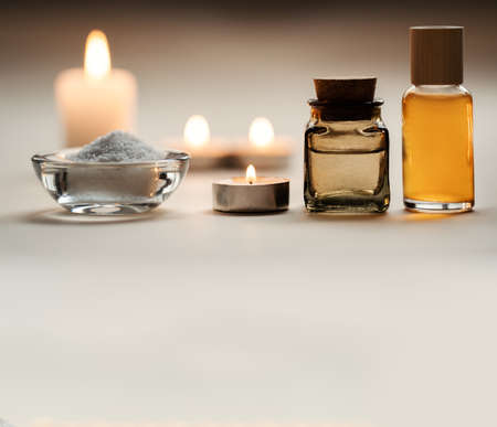 Beautiful spa composition with candles, oil flasks and bowl with salt. Pleasant beige background. Copy space. Standard-Bild