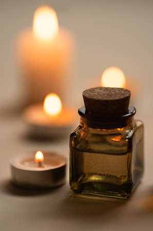Tranquil and concise spa composition with oil flask and candles. Copy space Standard-Bild