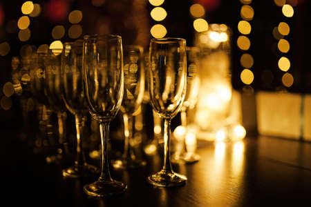 Champagne glasses on black background with bokeh lights. Party and holiday celebration concept. Standard-Bild