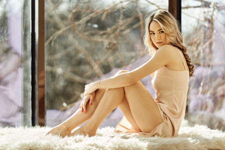 Young beautiful woman sitting on a sunny balcony in a beige silk nightie