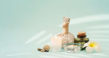 Concise spa composition with candles, flower, oil flask, herbal ball, and other decor elements on turquoise background.