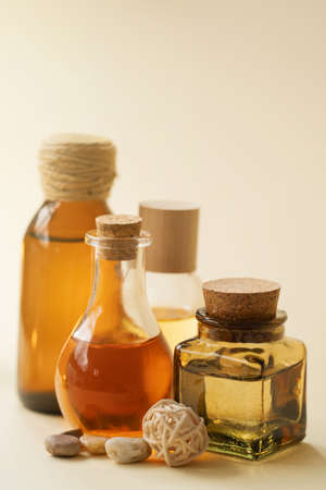 Concise spa composition with oil flasks on beige background. Standard-Bild