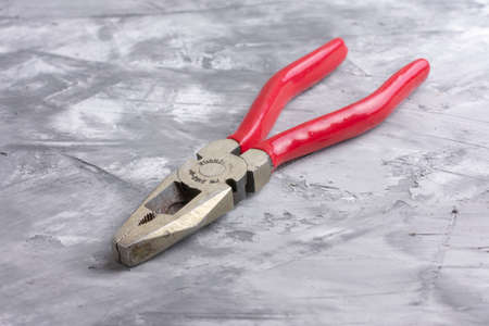 Pliers with red handles on a gray background,macro