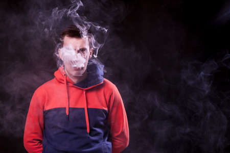 A young dark-haired man with sad eyes in a colored orange and blue hoody standing with arms behind smokes a vape and exhales a white smoke on a black isolated background