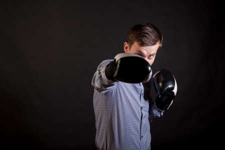 Dark-haired man in a plaid shirt with boxing gloves on his hands stabs on black isolated background