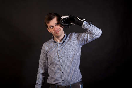 Dark-haired man in a plaid shirt with boxing gloves on his hands beats himself on black isolated background