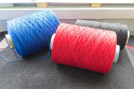 Three Bobbins with colored threads in the studio