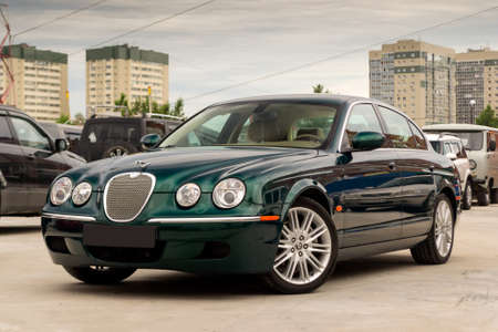 Brightly green Jaguar S-type 2007 front view with light beige interior in excellent condition in a parking space among other cars
