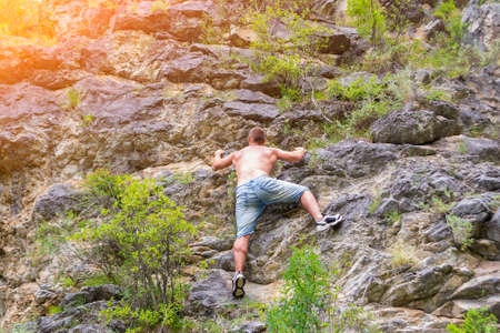 Young man climber in jeans shirts and bare torso climbs on rocks to the top in mountains of Altai without equipment and insurance