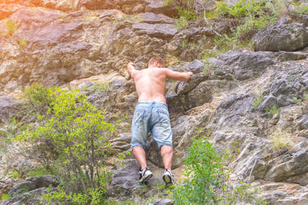 Young boy climber in jeans shirts and bare torso climbs on rocks to the top in mountains of Altai without equipment and insurance Banco de Imagens