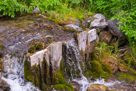 A small waterfall between the stones and two wooden planks among the green grass from a creek with clear mountain water in the mountains of the Altai Stock Photo