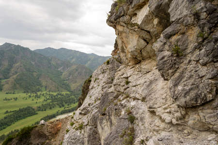 View from the top of the Altai mountains in Siberia with green plants and trees near the river of the katun with stones and caves