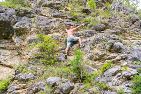 Young man climber in jeans shirts and bare torso climbs on rocks to the top in mountains of Altai without equipment and insurance points with his hand to the side
