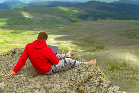 businessman in a red sweatshirt is sitting on a rock on a mountainside barefoot in seclusion with a noteboock in hand against a background of a green valley of hills.the manager works in the open air 版權商用圖片