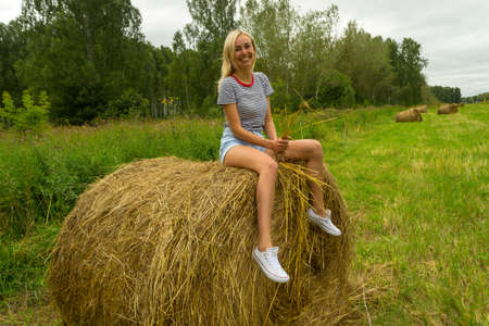 A beautiful blonde girl smiles and holds a bunch of grass between her legs and sits on a large round stack of dry hay collected smiling and on a summer or autumn afternoon Standard-Bild - 108966088
