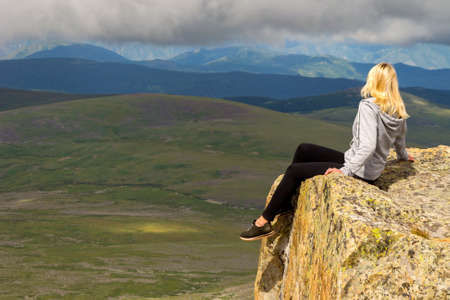 Blond woman sits dangerously alone on the edge of the cliff above the abyss in the mountains of Altai, hanging her legs down over the lake and looking out into the clouds on the peaks of the hills