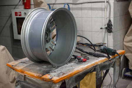 Automotive alloy cast aluminum rim on a workbench with tools for recovering and repairing after a breakdown when getting into a hole in a car repair shop Standard-Bild