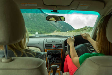 Two young beautiful girls traveling by car in the mountains of the Altai are driving by serpentine road