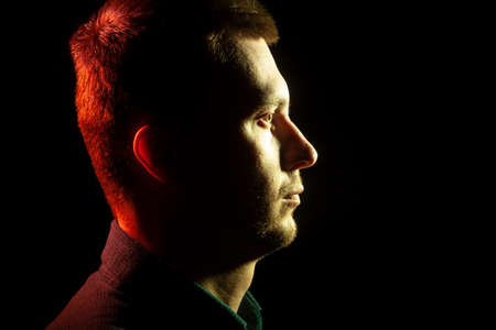 Close-up of the profile of an unshaven face of a man with stubble dressed in a shirt in the dark, illuminated from the front by a yellow back red on a black isolated background Stock Photo