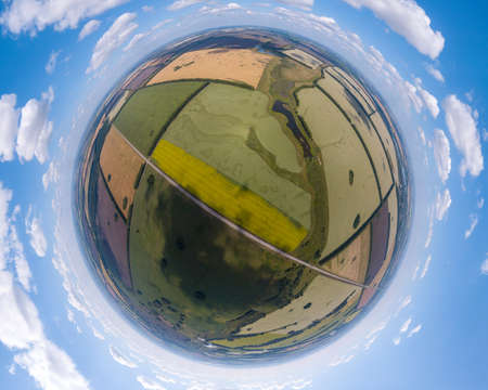 Aerial view of agricultural fields of different color crop under a clear blue sky with clouds on a sunny warm day. Panorama 360 degrees.