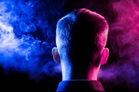 Una vista desde la parte posterior de la cabeza de un hombre con una camisa fumando un vape y exhalando humo multicolor de azul y rojo en diferentes direcciones de él sobre un fondo negro aislado